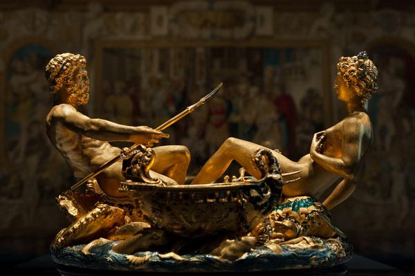 """A Saliera de Benvenuto Cellini. Ao fundo, a tapeçaria """"A Unidade do Estado"""", representando Francisco I de França, de Francesco Primaticcio, Rosso Fiorentino e Claude Badouin, entre outros. © Kunsthistorisches Museum"""